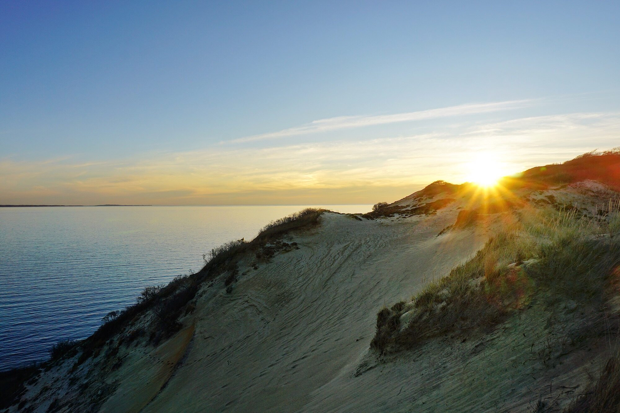 Sunrise over a coastal bank in Menemsha Hills, on Martha's Vineyard, with a view of the ocean