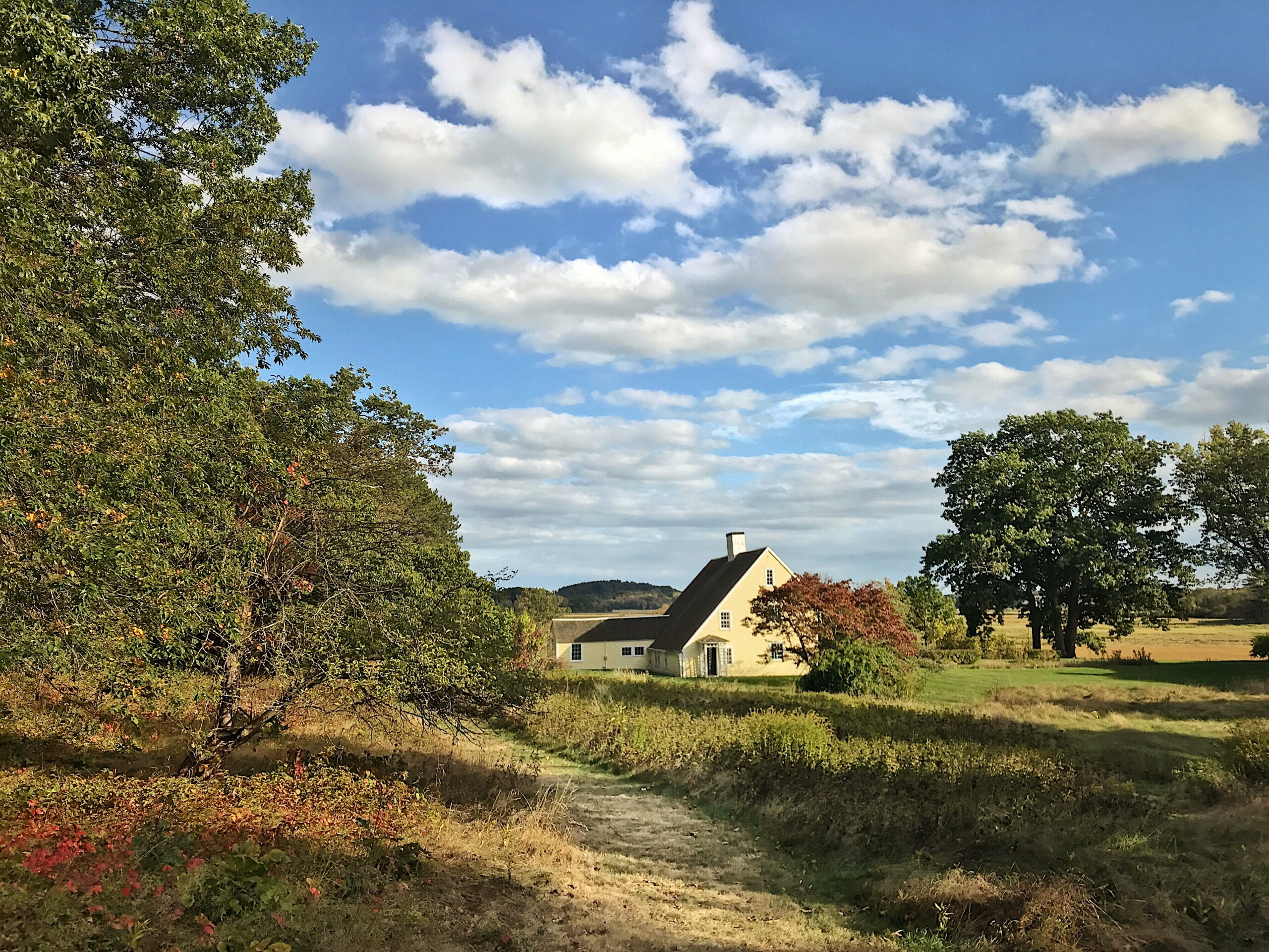 farm lands with a house and blue skies