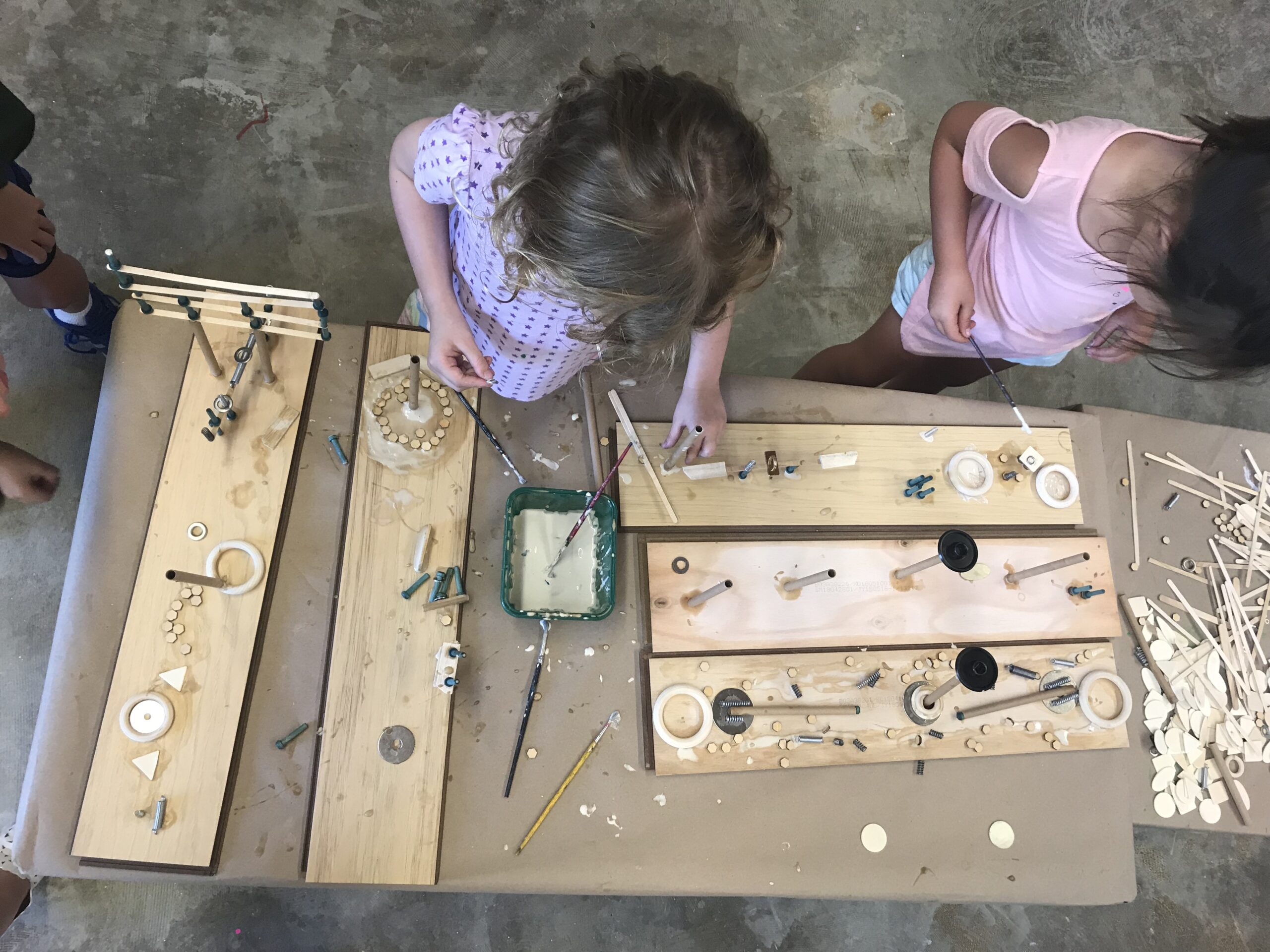 children work on a project with wood and paint