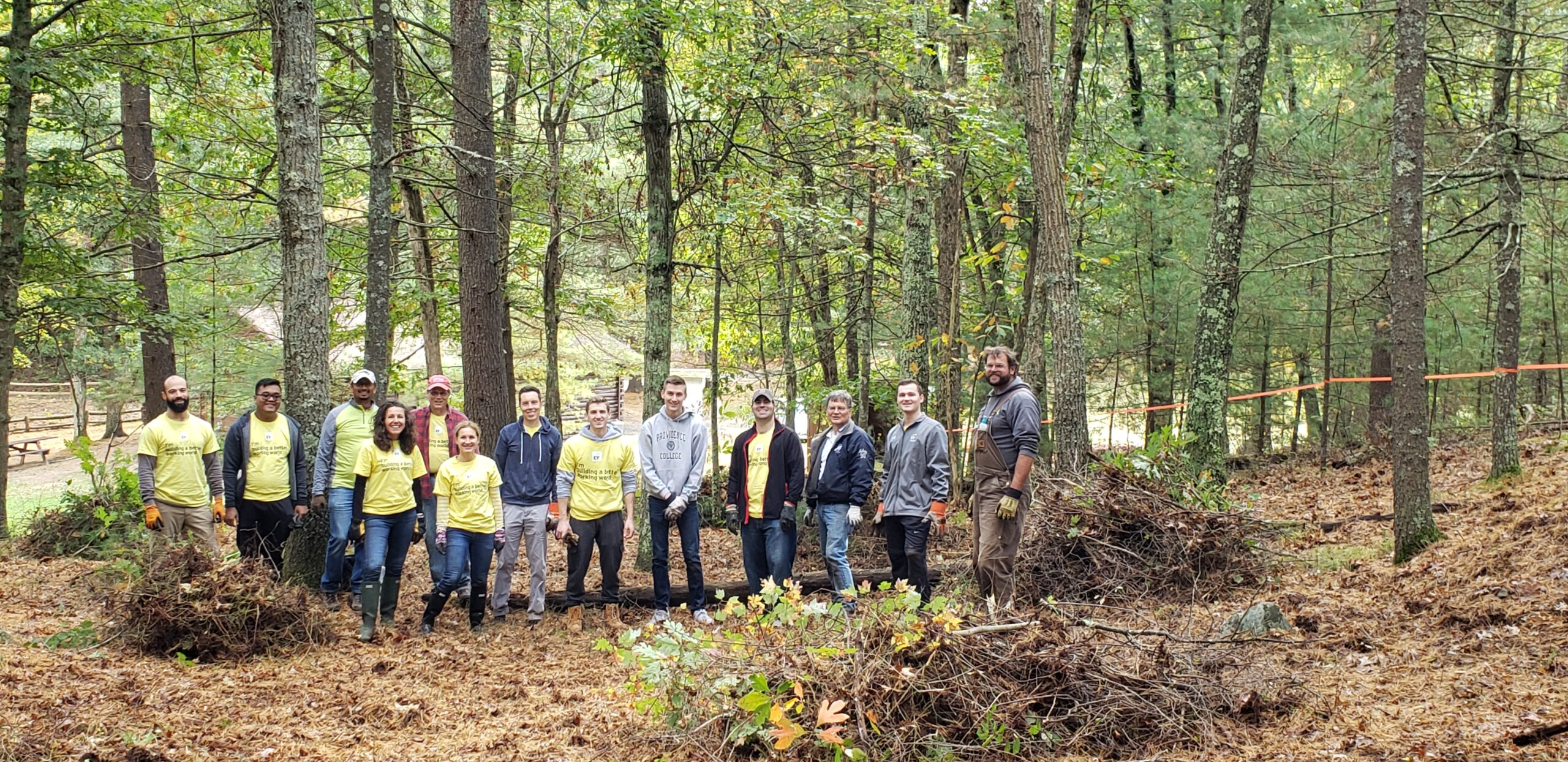 A group of volunteers stands in Rocky Woods