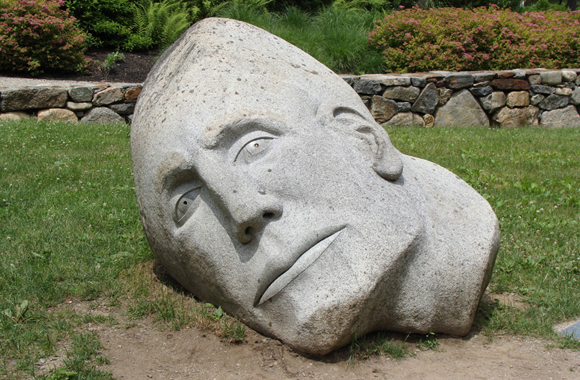 a granite face with his ear to the ground