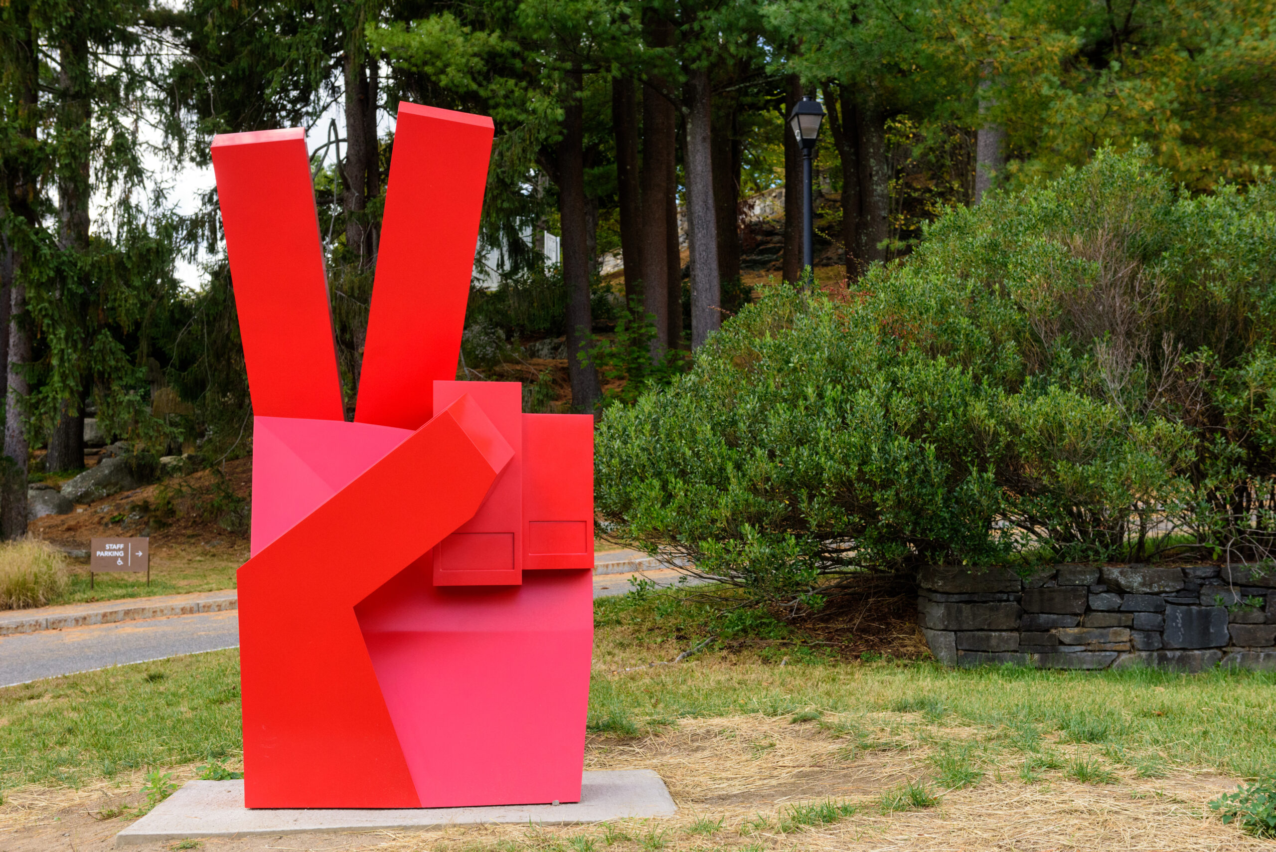 a large, bright red hand, throws a piece sign in the Sculpture Park