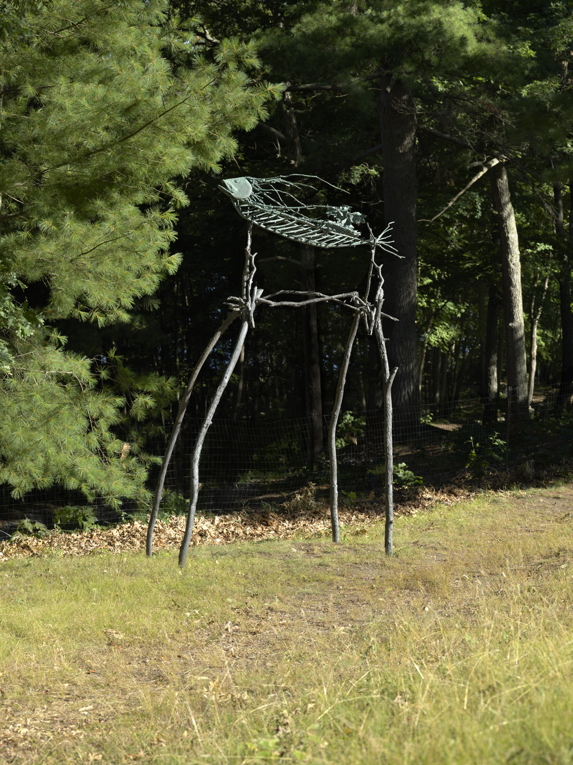 a bronze sculpture in a field