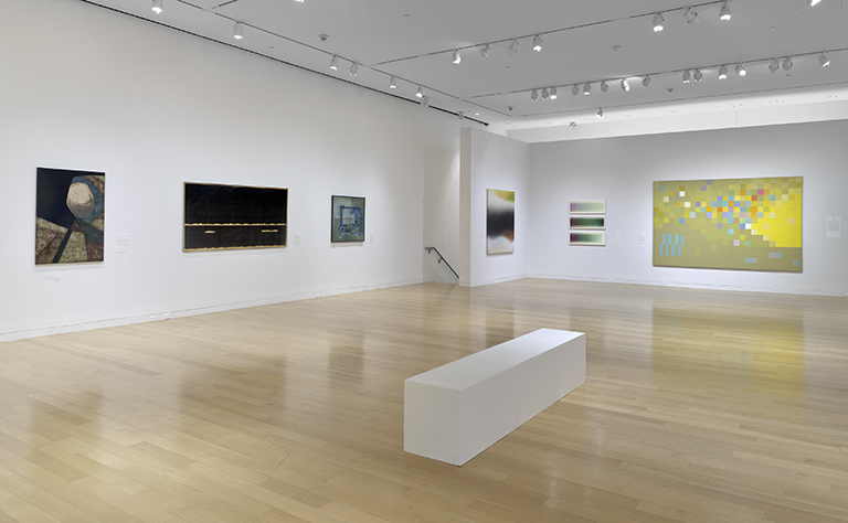 a view of the gallery with white walls and multi colored paintings