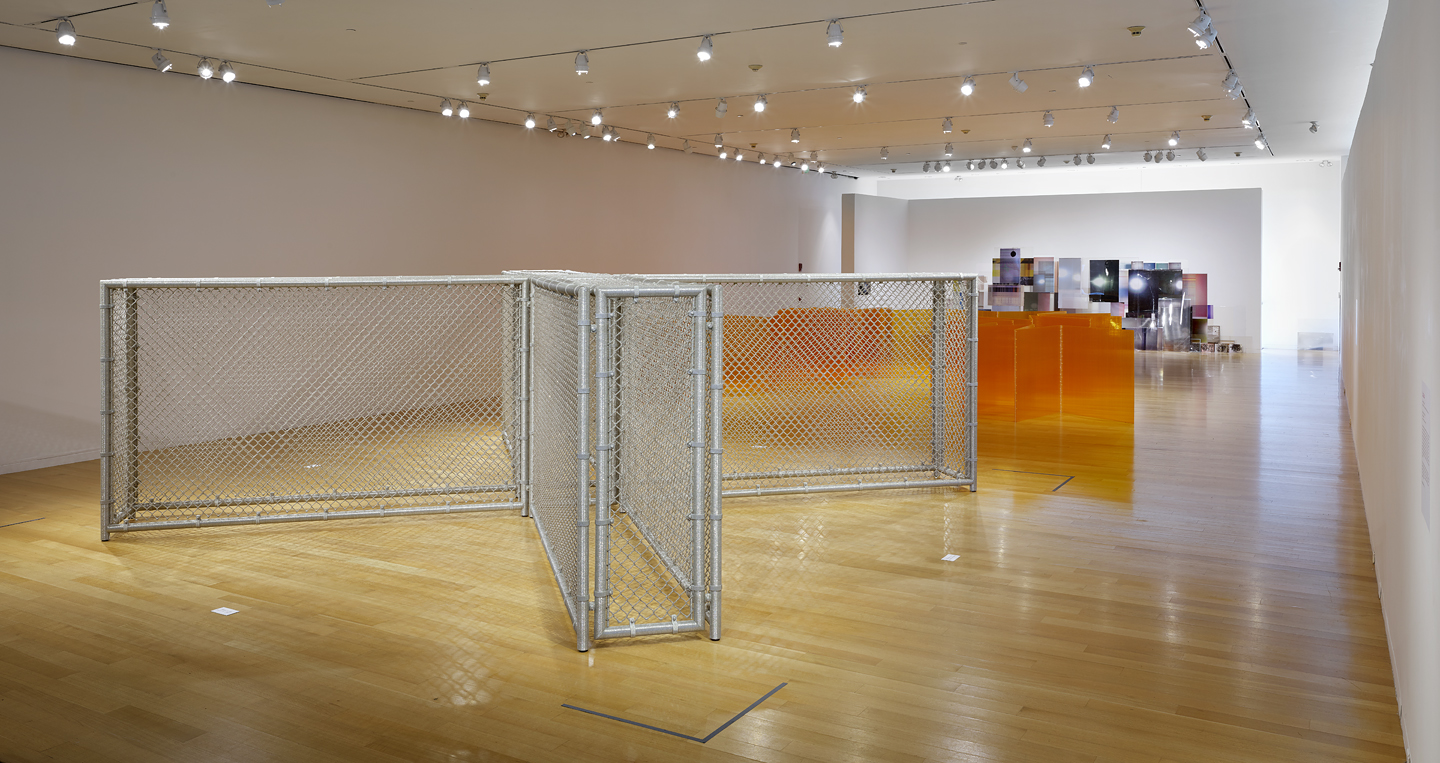 an installation view with fences and bright screens in a clean white gallery